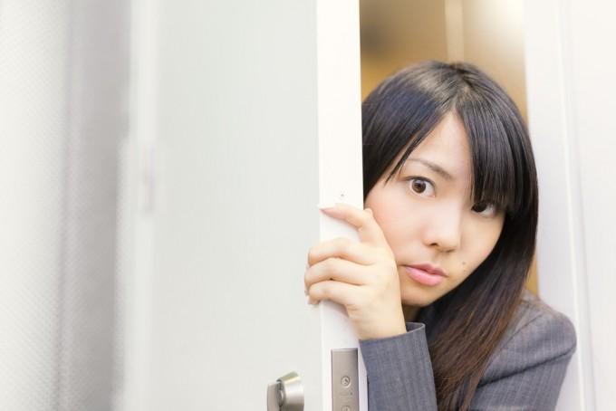 会議の様子をドアの隙間から覗く女性社員
