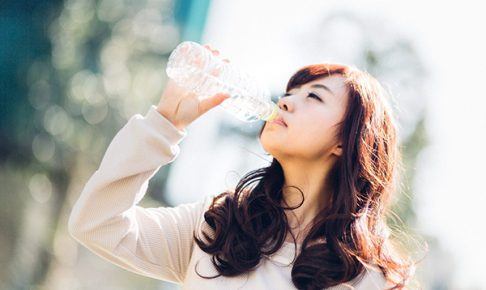 ミネラルウォーターを飲む若い女性