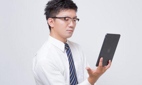 iPad mini で電子書籍を読むビジネスマン